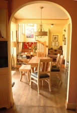 Pacific-Madrone-Bench-Chairs-and-Dutch-Pullout-Extension-Dining-Table-through-arch